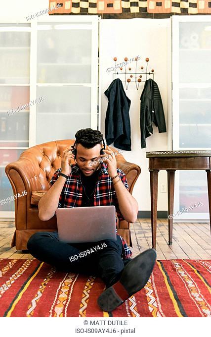 Man sitting on floor against armchair wearing headphones using laptop