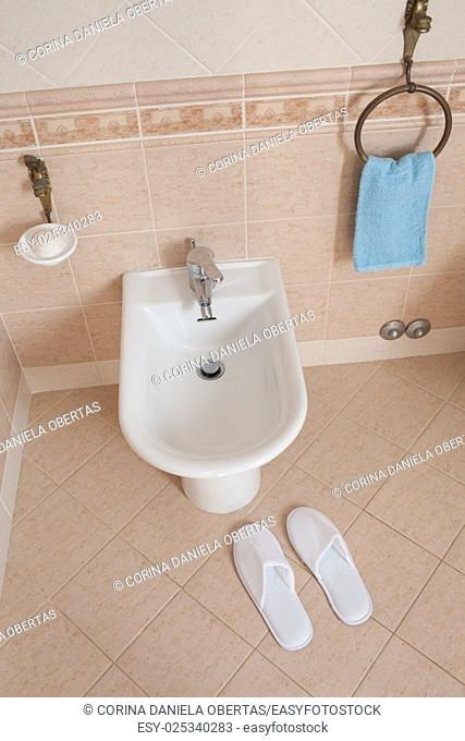 Spa-styled slippers near the bidet inside home bathroom