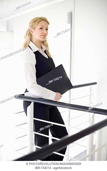 Businesswoman leaning against a railing with briefcase under her arm