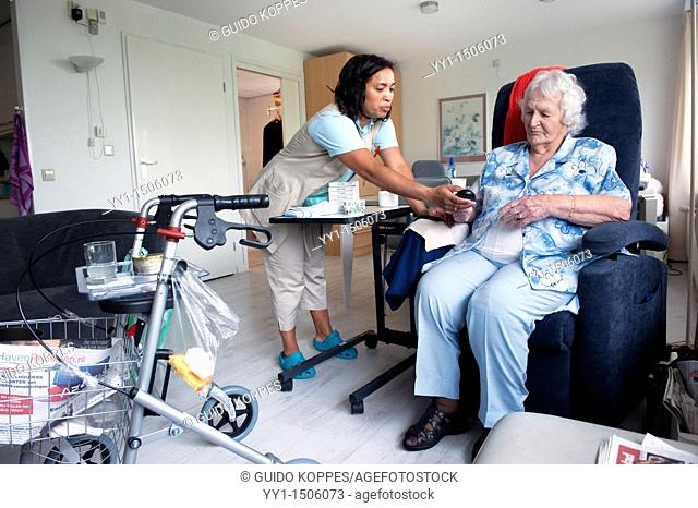 Rotterdam, Netherlands. A professional nurse of a Rotterdam nursing home helping an elderly inhabitant with the controls of her chair