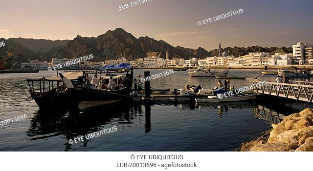 Mutrah Fish Market. Fishing boats landing catch with waterside buildings behind