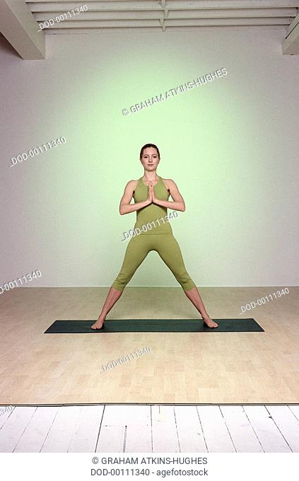 Stay Young, Warrior, woman standing on green mat, facing forward, feet three meters apart, palms of hands together in Prayer pose