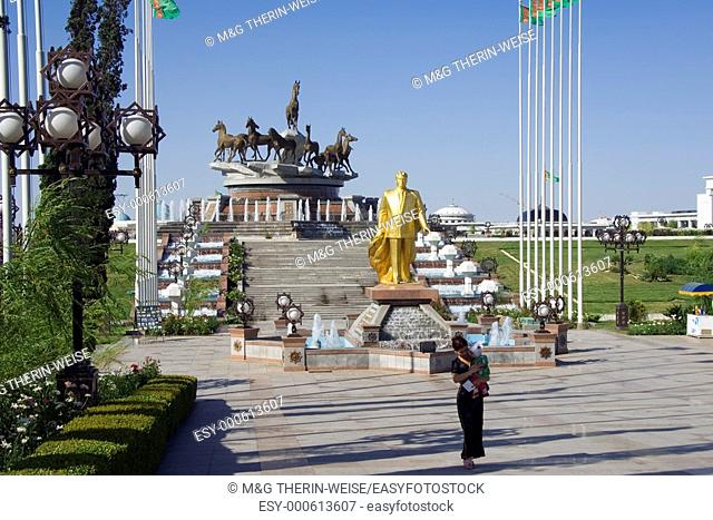 Gold covered statue of President Turkmenbasy in front of the monument of the 10th anniversary of Independence, Akhal-teke horses fountain, Ashgabat