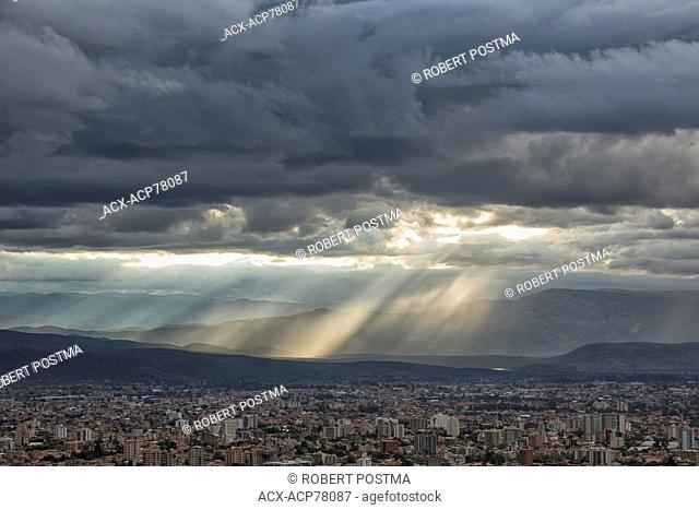 Shafts of light shne down through storm clouds over top of Cochabamba, Bolivia