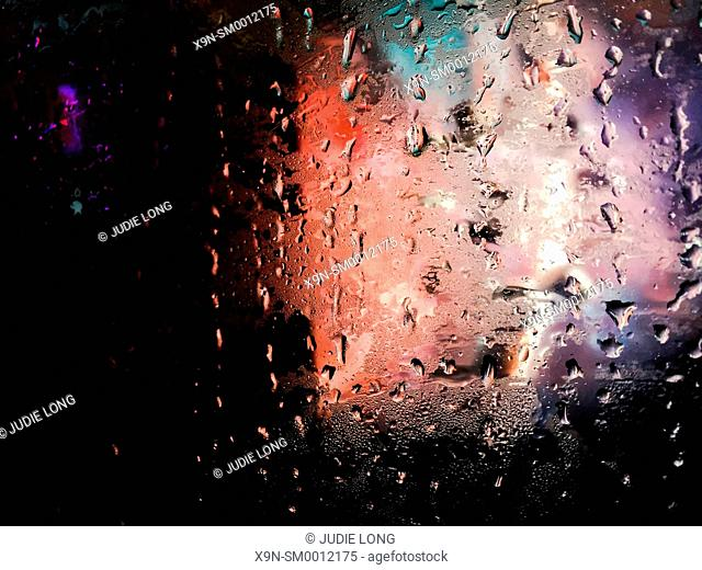 Looking out the rain covered window of a New York City Bus traveling down Ninth Avenue. people walking in the rain