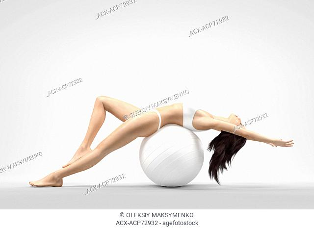 Young beautiful woman with fit slim body stretching balancing on white exercise ball isolated on white background. Fitness and health concept