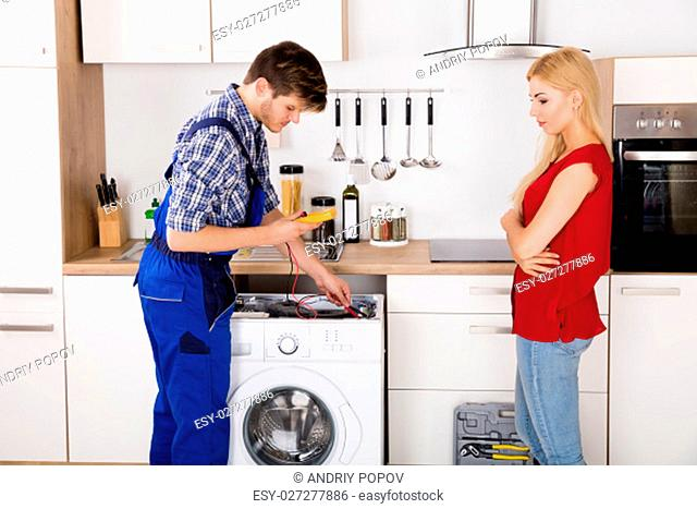 Young Woman Looking At Male Worker Repairing Washing Machine With Multimeter In Kitchen