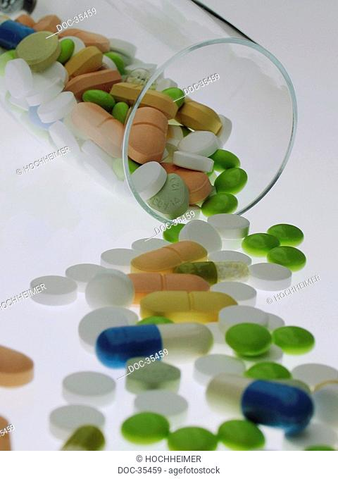 Different kinds of pills spread out in front of a fallen glas