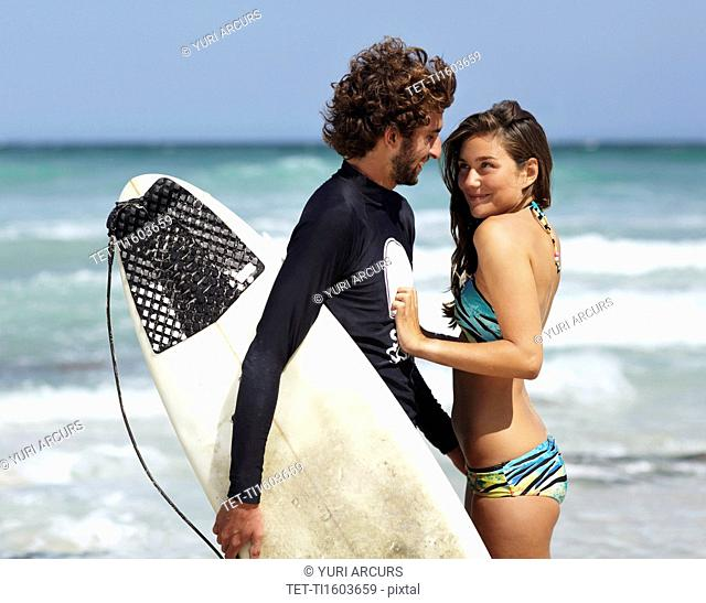 Surfer man and young woman on beach