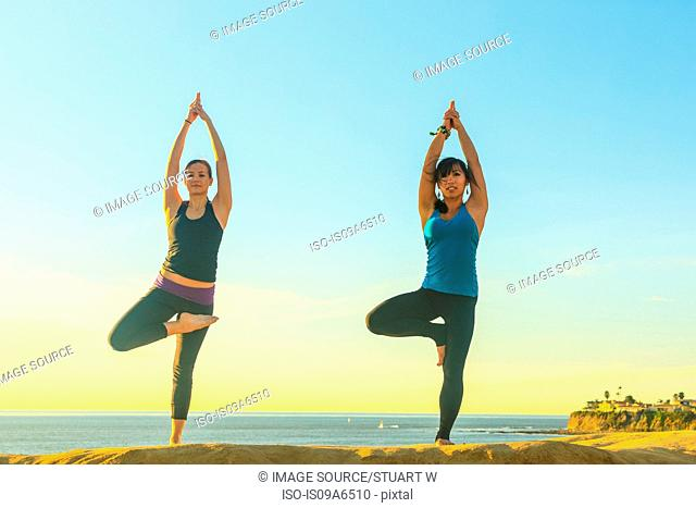 Women practicing yoga on rock formation