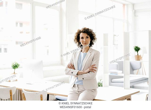 Businesswoman in office sitting on desk with arms crossed