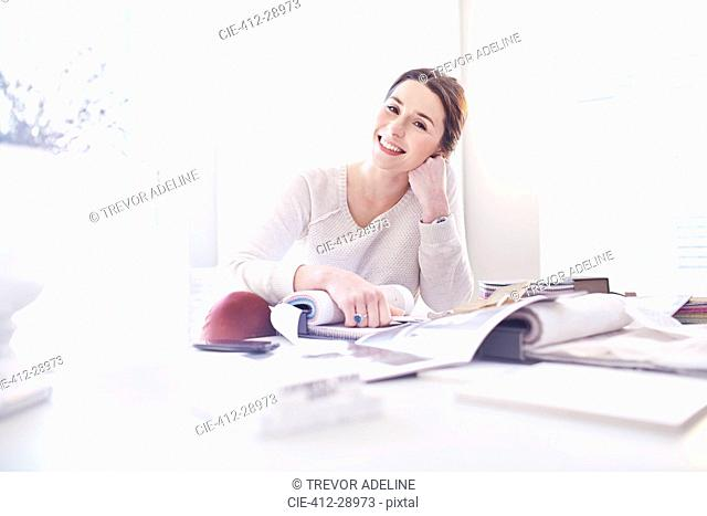 Portrait smiling interior designer with swatches in office