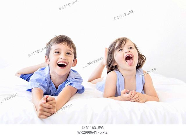 Boy and young girl with brown hair lying side by side on a bed, mouth open, sticking out tongue