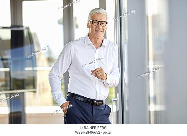 Businessman in office leaning against window, smiling