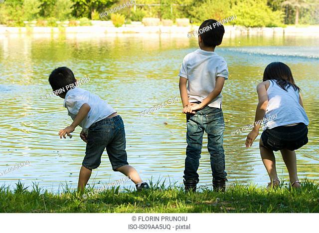 Three children playing by lake
