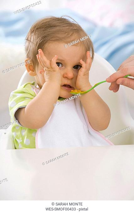 Human hand feeding baby girl 6-11 months
