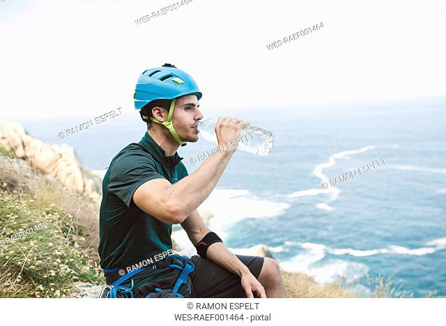 Climber at the coast drinking water