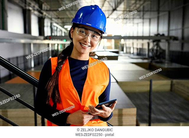 Portrait of confident female worker in factory warehouse