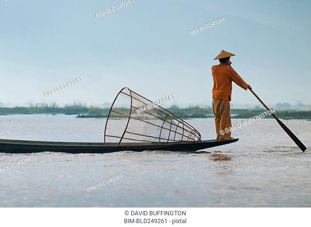 Man standing on bow of boat in river holding paddle