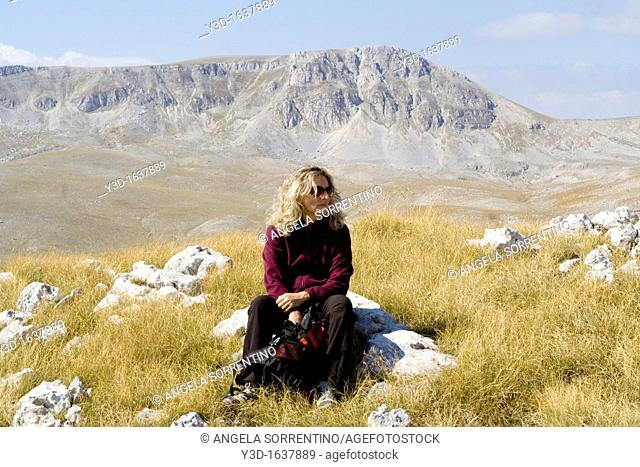 Woman contemplating nature, outdoors with open space and a big mountain in the background called Mount Greco, Abruzzi region, Italy