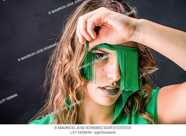 Young woman looking out from a blindfold of green fringes