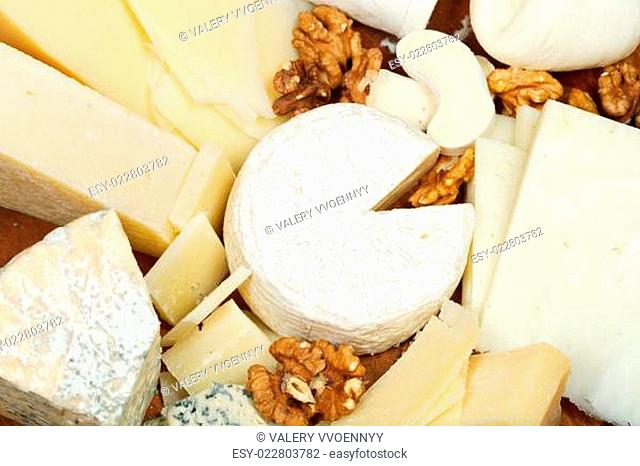 assortment of cheeses on wooden plate