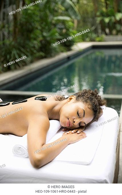 Relaxed woman receiving stone therapy at day spa