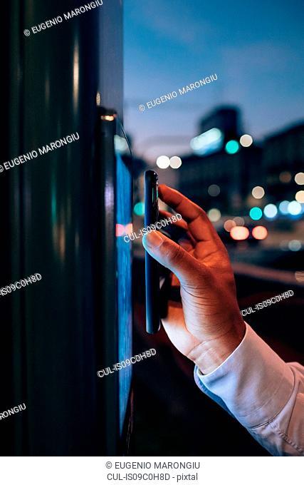 Businessman using digital information system at bus stop