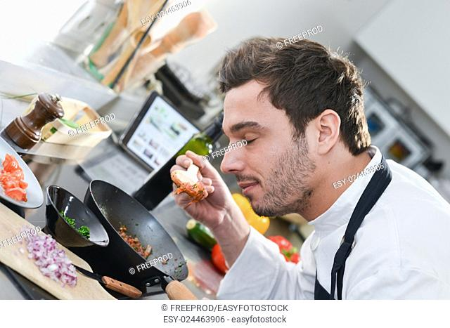 Man happy in kitchen tasting with a wooden spoon in stove