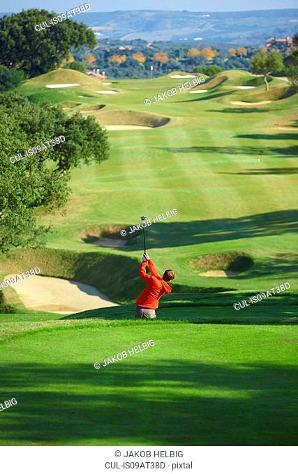 High angle view of golf course and golfer taking golf swing