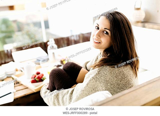 Portrait of smiling woman sitting on balcony