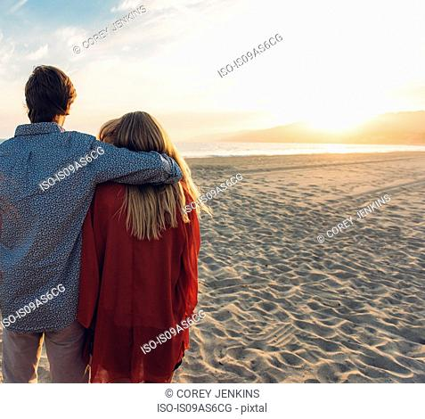Young couple standing on beach, hugging, rear view