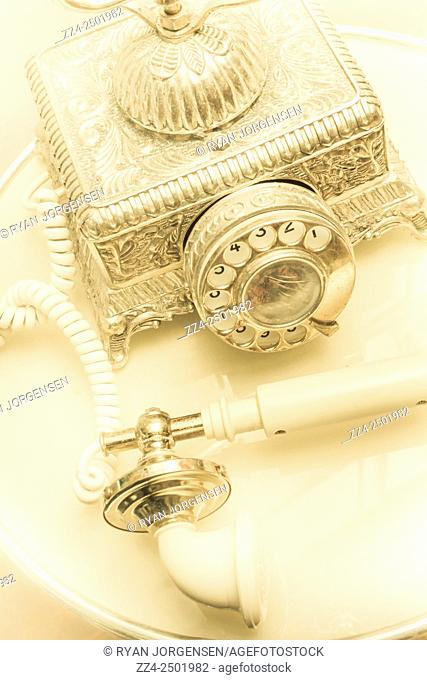 Retro silver and gold telephone placed on classic stylized table with receiver disconnected. Off the hook