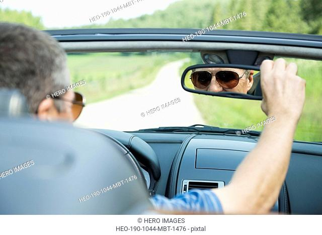 Portrait of man looking through rear-view mirror in convertible