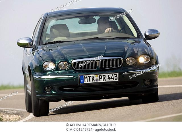Jaguar X-Type 2.2D, model year 2006-, dark green, driving, diagonal from the front, frontal view, country road