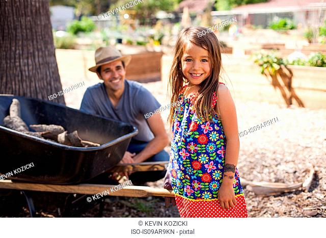 Portrait of girl in community garden with father and wheelbarrow