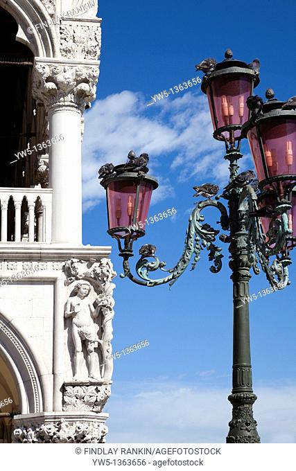 Carving on a Doge's Palace in St Mark's Square, Venice with lamp post and pigeons, Italy