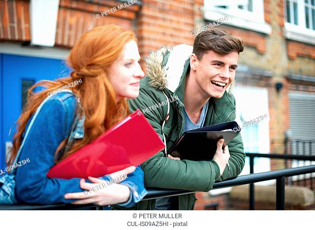 Young college student couple leaning against campus handrail