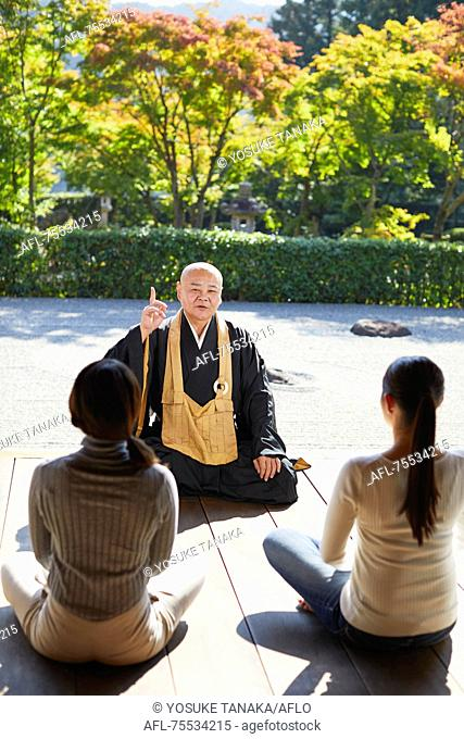 Japanese priest preaching to women at a temple
