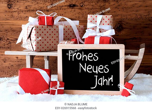Chalkboard With German Text Frohes Neues Jahr Means Happy New Year. Sled With Christmas And Winter Decoration. Gifts And Presents On Snow With Wooden Background