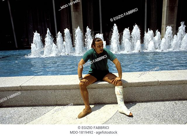 Italian singer-songwriter Eros Ramazzotti sitting by a fountain with his left leg put in plaster. New York, 26th July 1991