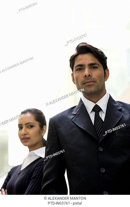 Businessman in suit in foreground with businesswoman behind