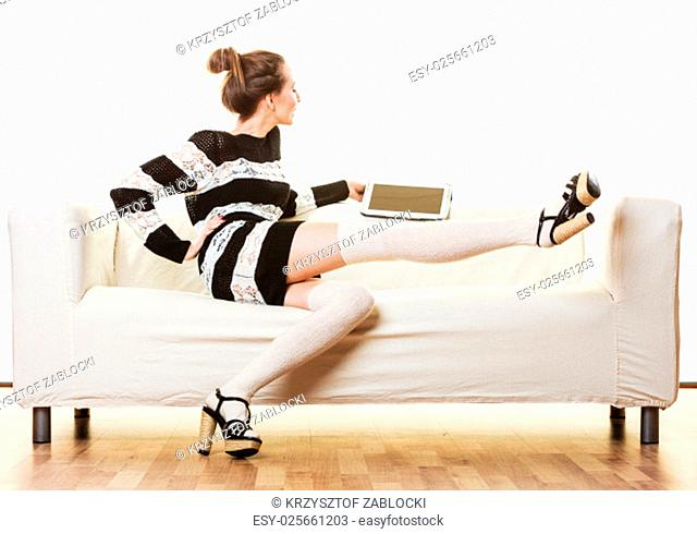 internet technology concept. fashion trends woman sitting with a tablet on a white couch at home