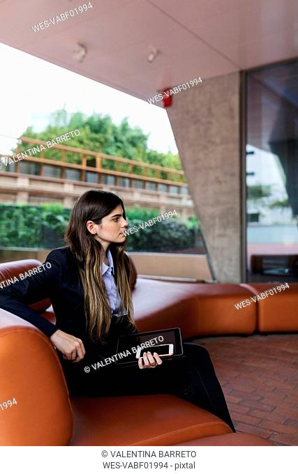Young businesswoman sitting in a lounge holding cell phone and tablet