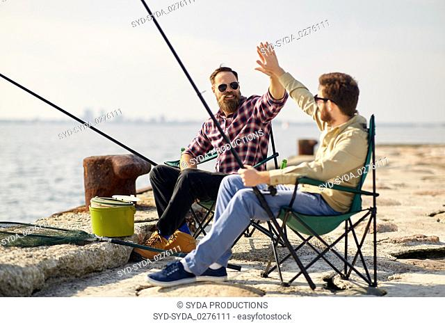 happy friends with fishing rods on pier