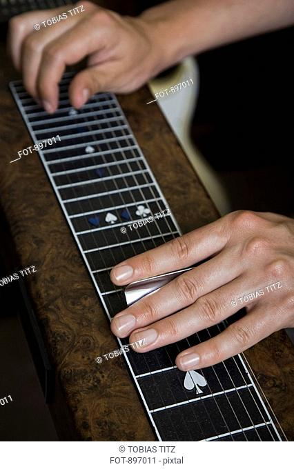 Detail of a man playing a slide guitar