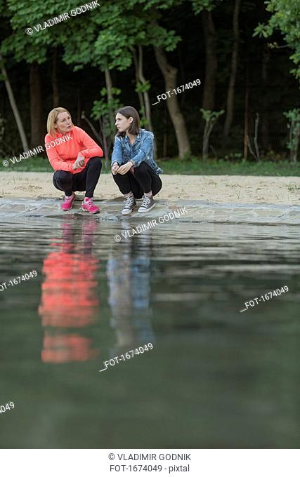 Full length of mother and daughter talking while crouching at lakeshore in park