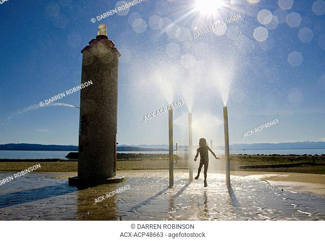 Young child plays in the water park at Willingdon Beach in Powell River on British Columbia's Sunshine Coast, in the Vancouver, Coast & Mountains region, Canada
