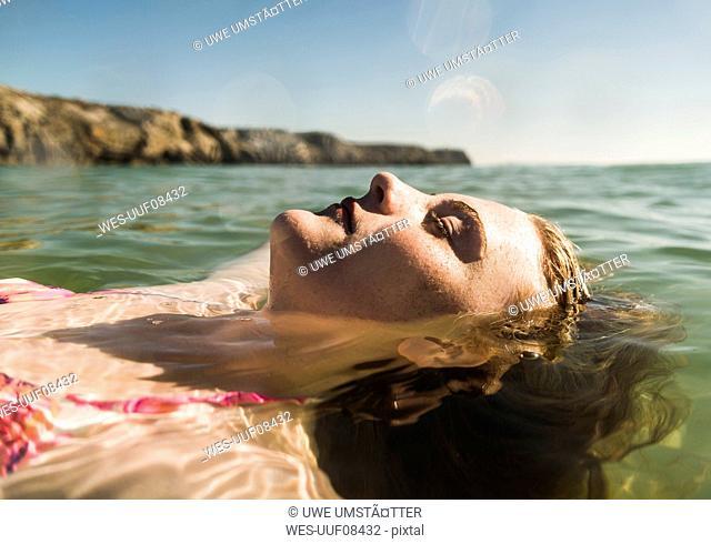 Teenage girl floating in the sea