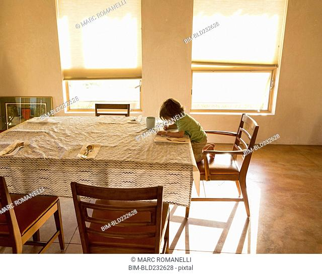 Caucasian boy drawing at table
